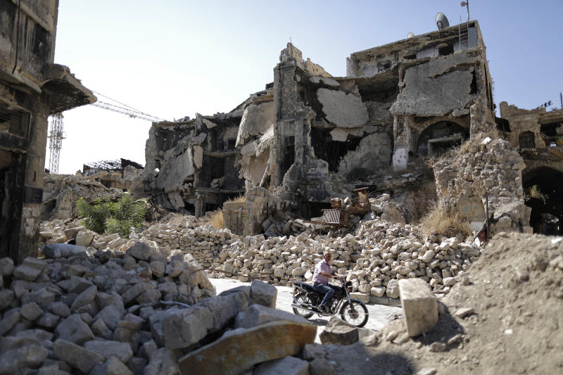 In this Saturday, July 27, 2019 photo, a man rides his motorcycle through the rubble of the old city of Aleppo, Syria. Rebels still frequently strike with shelling and mortars into Aleppo, killing civilians nearly three years after the government recaptured the city. Aleppo is a symbol of how President Bashar Assad succeeded in turning the tide in Syria's long civil war with a series of wins, but it's equally a symbol of how he's been unable to secure a final victory. Half of Aleppo remains in ruins, and rebels remain on the doorstep. (AP Photo/Hassan Ammar)