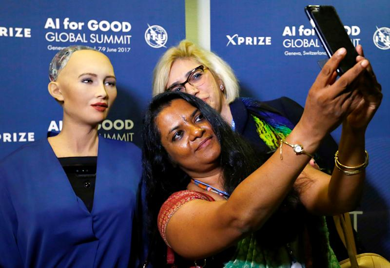 "Attendees pose with Sophia, a robot integrating the latest technologies and artificial intelligence developed by Hanson Robotics during a presentation at the ""AI for Good"" Global Summit at the International Telecommunication Union (ITU) in Geneva, Switzerland June 7, 2017. REUTERS/Denis Balibouse"