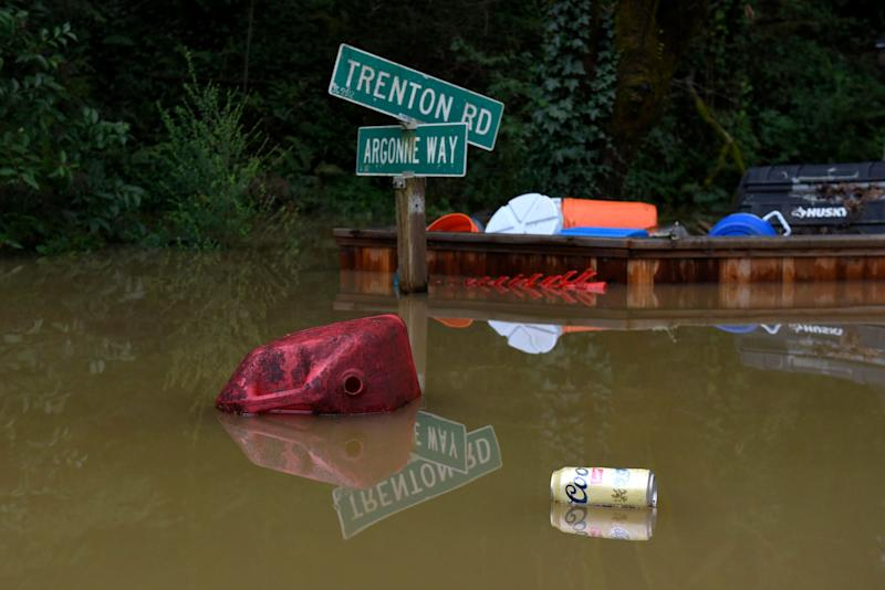 Debris float past a street sign in the flood waters of the Russian River in Forestville, Calif., on Feb. 27, 2019. (Photo: Michael Short/AP)