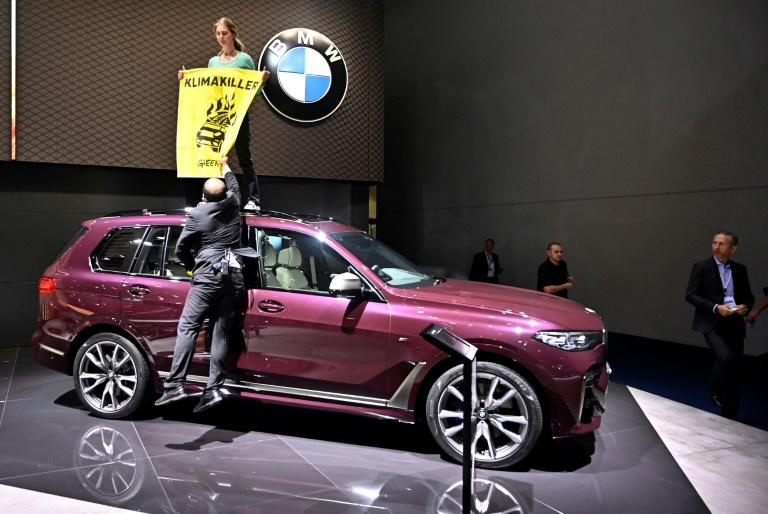 A Greenpeace activist protested at the Frankfort motor show earlier this week by standing on top of a SUV on display with a poster that read 'Climate Killers' (AFP Photo/Tobias SCHWARZ)
