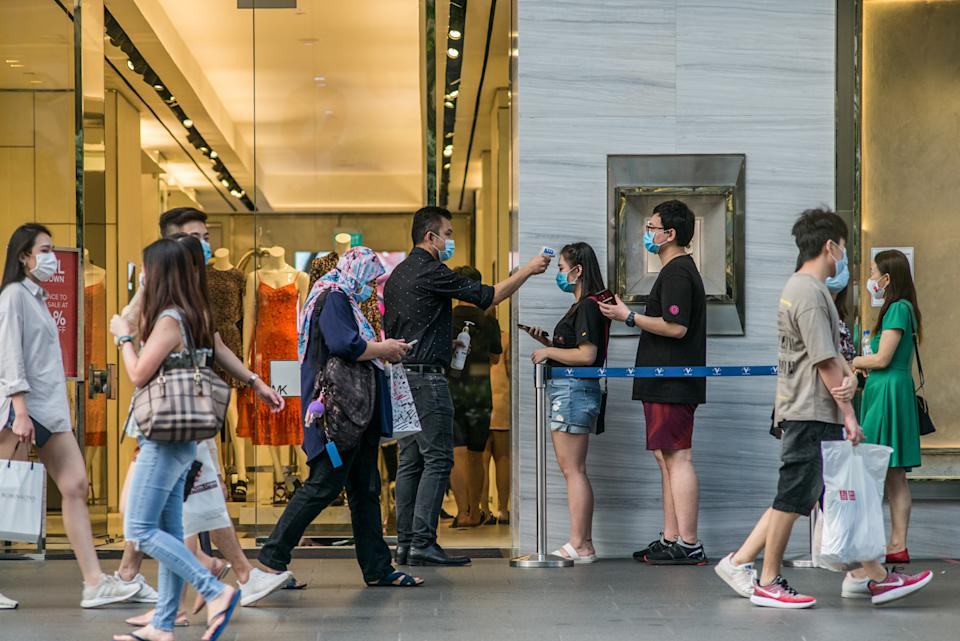 People wearing face masks are scanned for their temperatures before entering a shopping mall along Orchard Road in Singapore.