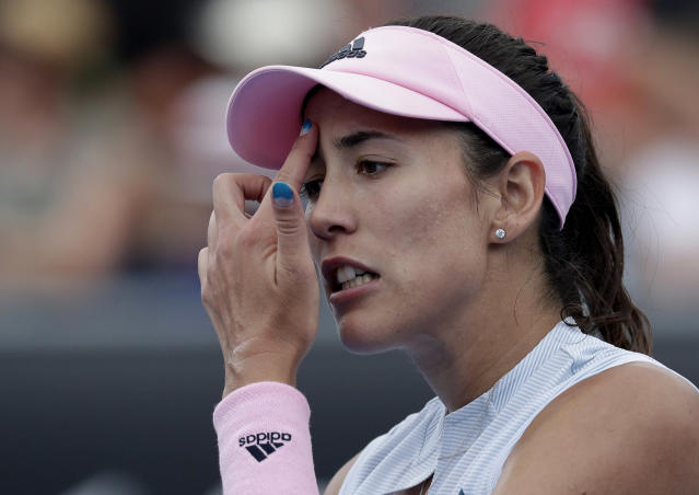 Spain's Garbine Muguruza wipes sweat from her face during her first round match against China's Zheng Saisai at the Australian Open tennis championships in Melbourne, Australia, Tuesday, Jan. 15, 2019. (AP Photo/Kin Cheung)