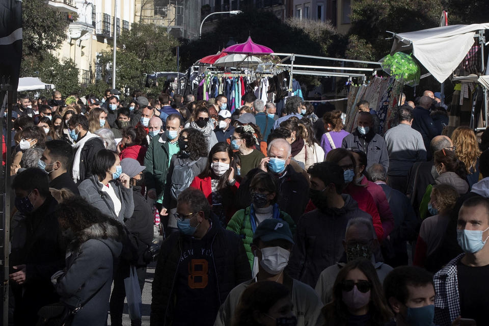 People walk in the Rastro flea market in Madrid, Spain, Sunday, Nov. 22, 2020. Madrid's ancient and emblematic Rastro flea market reopened Sunday after a contentious eight-month closure because of the COVID-19 pandemic that has walloped the Spanish capital. (AP Photo/Paul White)