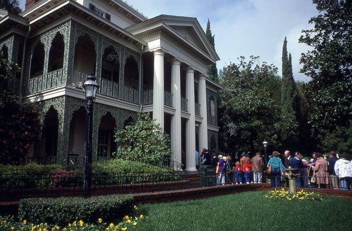 Park goers waiting in line to enter the Haunted Mansion attraction at Disneyland in 1980