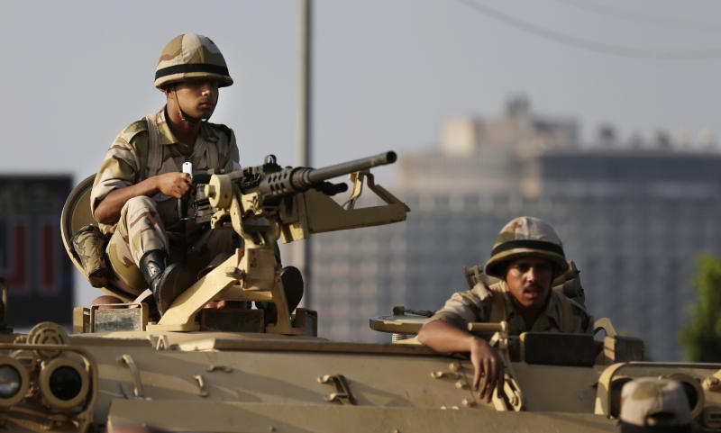 Egyptian army soldiers take their positions on top of their armored vehicle to guard the entrances of Tahrir square, in Cairo, Egypt, Monday, July 8, 2013. Egyptian military officials said gunmen killed at least five supporters of the former president when people tried to storm a military building in Cairo. The official, who declined to be named because he was not authorized to brief reporters, also said a group had tried to storm the headquarters of the Republican Guard. He added that those killed had been supporters of former President Mohammed Morsi camped outside the building in protest at his overthrow. (AP Photo/Hassan Ammar)