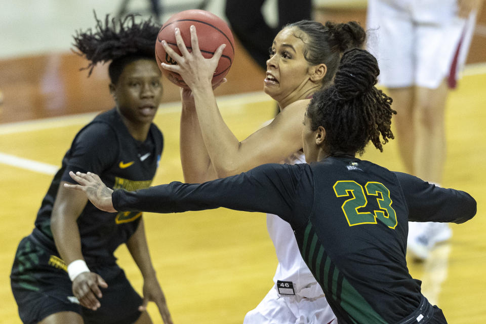 Arkansas guard Chelsea Dungee, center, goes to the basket between Wright State center Jada Wright (23) and guard Emani Jefferson during the first half of a college basketball game in the first round of the women's NCAA tournament at the Frank Erwin Center in Austin, Texas, Monday, March 22, 2021. (AP Photo/Stephen Spillman)