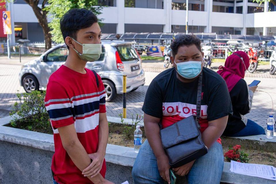 Ahmad Rasdan (right) and Mohd Shafiq Abdul Rahim speak to reporters outside the Axiata Arena Covid-19 vaccination centre in Bukit Jalil September 23, 2021. — Picture by Shafwan Zaidon