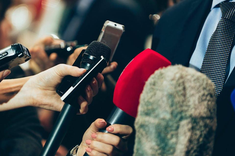 A group of journalists holding microphones during a media scrum.