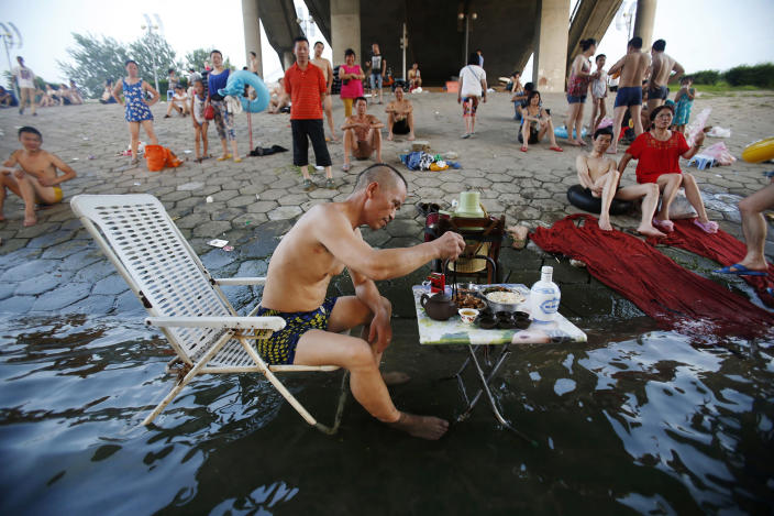 <p>A man sitting on a beach chair in his swimming trunks takes his meal at a small table partially dipped into the Hanjiang river to escape the summer heat, as other swimmers look on under a bridge in Wuhan, Hubei province, China, July 28, 2013. The highest temperature in Wuhan reached 37 degrees Celsius (98.6 degrees Fahrenheit) on Sunday, local media reported. (China Daily/Reuters) </p>