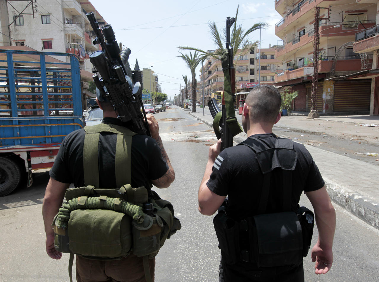 Two Sunni gunmen stand in the middle of Syria Street which divides the Sunni and Alawite areas, in the northern port city of Tripoli, Lebanon, Sunday May 13, 2012. Gunfire broke out in the city Saturday and continued through the night primarily between a neighborhood populated by Sunni Muslims who hate Syrian President Bashar Assad and another area with many Assad backers from his Alawite sect. Lebanon's national news agency NNA said one soldier was shot dead by a sniper in the city early Sunday. Another man was found dead on the side of a road while a third died after a shell landed in a residential neighborhood. (AP Photo/Hussein Malla)