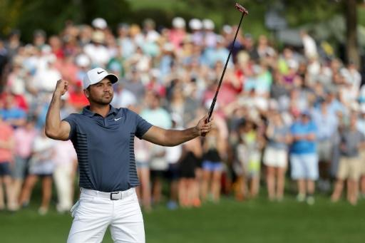 Jason Day of Australia reacts following his par putt on the 18th green