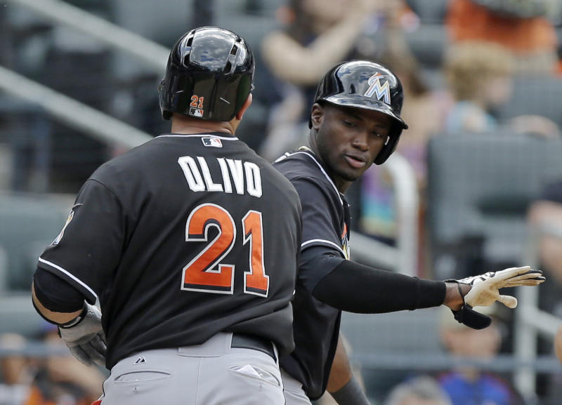 Miami Marlins Adeiny Hechavarria congratulates Marlins Miguel Olivo (21) after scoring on Olivo's tenth-inning, two-run home run off New York Mets relief pitcher Robert Carson in a baseball game in New York, Sunday, June 9, 2013. (AP Photo/Kathy Willens)