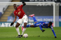 Manchester United's Paul Pogba, left, duels for the ball with Leicester's Kelechi Iheanacho during the English FA Cup quarter final soccer match between Leicester City and Manchester United at the King Power Stadium in Leicester, England, Sunday, March 21, 2021. (AP Photo/Ian Walton, Pool)
