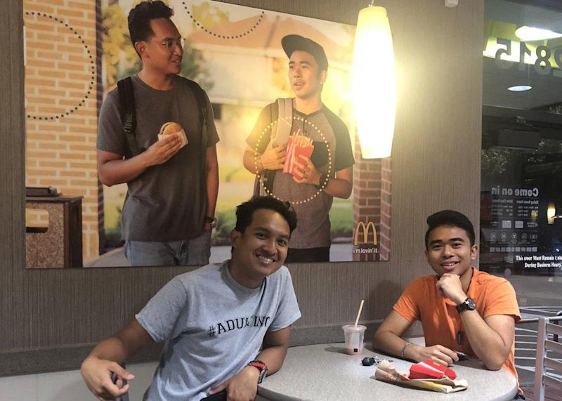 Jevh Maravilla and his friend, Christian Toledo pose with their fake poster in a Houston McDonald's: Twitter/@JevHolution