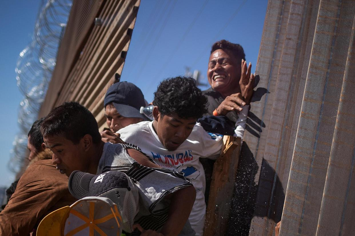 Migrants, part of a caravan of thousands from Central America trying to reach the United States, return to Mexico after being hit by tear gas by U.S. Customs and Border Protection (CBP) after attempting to illegally cross the border wall into the United States in Tijuana, Mexico November 25, 2018. (Photo: Adrees Latif/Reuters)