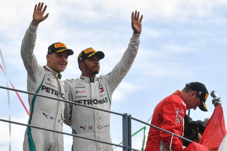 Mercedes' British driver Lewis Hamilton (C) and team-mate and third-placed Finnish teammate Valtteri Bottas celebrate on the podium after the Italian Formula One Grand Prix at the Autodromo Nazionale circuit in Monza on September 2, 2018