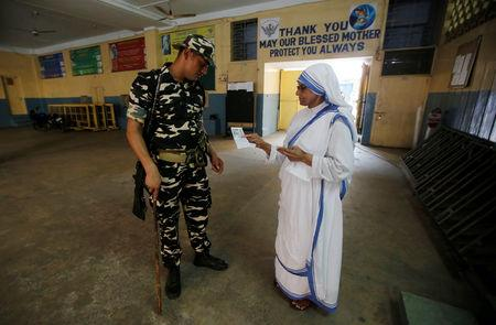 A security personnel checks an identity card of a catholic nun from the Missionaries of Charity as she arrives to cast her vote at a polling station during the final phase of general election in Kolkata, India, May 19, 2019. REUTERS/Rupak De Chowdhuri