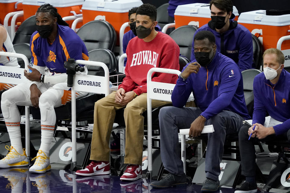 Phoenix Suns guard Devin Booker watches from the bench during the first half of an NBA basketball game against the Oklahoma City Thunder, Wednesday, Jan. 27, 2021, in Phoenix. (AP Photo/Matt York)