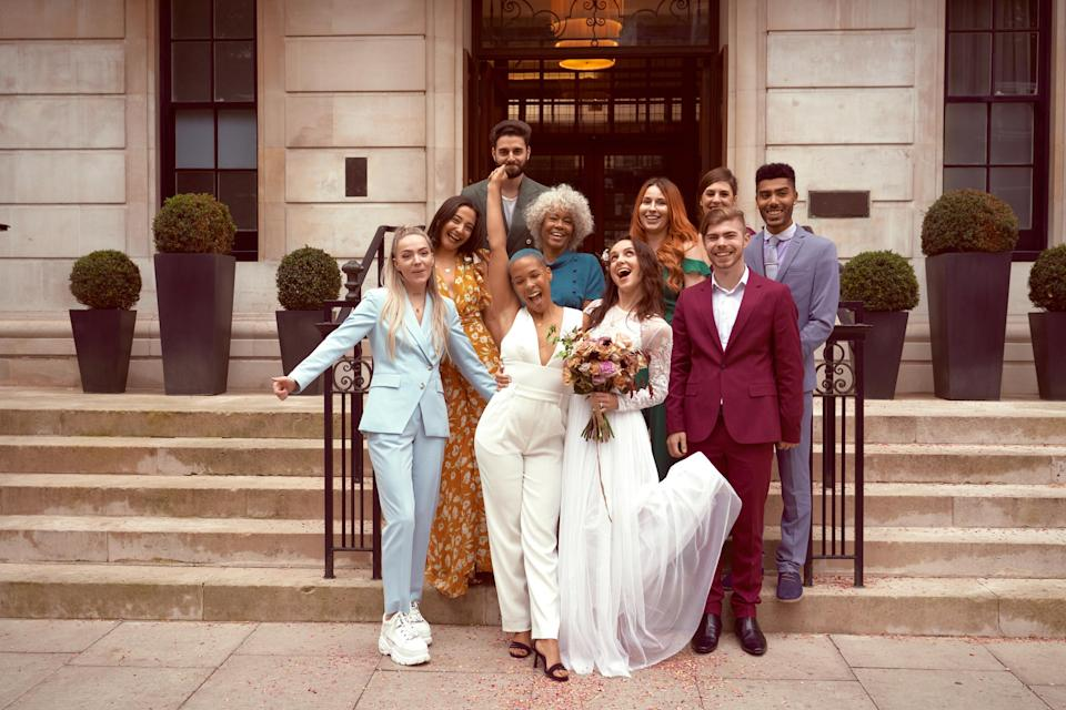 A wedding party of adults posing for a photo outside on steps