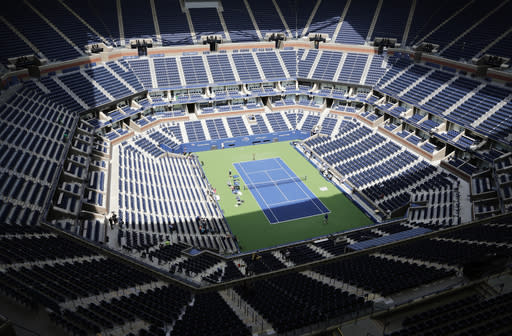 FILE - In this Aug. 27, 2017, file photo, players practice for the U.S. Open tennis tournament at Arthur Ashe Stadium in New York. As coronavirus cases spike in other parts of the country a month before the U.S. Open is supposed to start in New York, the U.S. Tennis Association said Friday, July 31, 2020, it continues its plans to hold its marquee event and another tournament beforehand. (AP Photo/Peter Morgan, File)