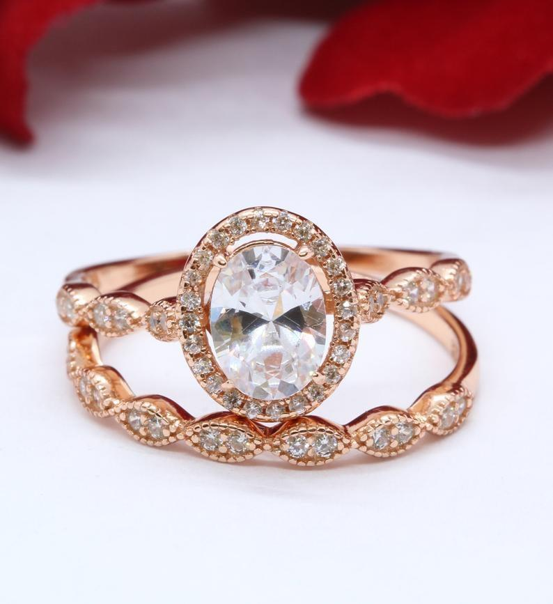 """<p>The <a href=""""https://www.popsugar.com/buy/Halo-Two-Piece-121-Carat-Oval-Simulated-Diamond-Rose-Gold-531249?p_name=Halo%20Two-Piece%201.21%20Carat%20Oval%20Simulated%20Diamond%20in%20Rose%20Gold&retailer=etsy.com&pid=531249&price=59&evar1=fab%3Aus&evar9=44555978&evar98=https%3A%2F%2Fwww.popsugar.com%2Fphoto-gallery%2F44555978%2Fimage%2F47011771%2FHalo-Two-Piece-121-Carat-Oval-Simulated-Diamond-in-Rose-Gold&list1=wedding%2Cjewelry%2Crose%20gold%2Cengagement%20rings&prop13=api&pdata=1"""" rel=""""nofollow noopener"""" class=""""link rapid-noclick-resp"""" target=""""_blank"""" data-ylk=""""slk:Halo Two-Piece 1.21 Carat Oval Simulated Diamond in Rose Gold"""">Halo Two-Piece 1.21 Carat Oval Simulated Diamond in Rose Gold</a> ($59) comes complete with both a band and a engagement ring. </p>"""