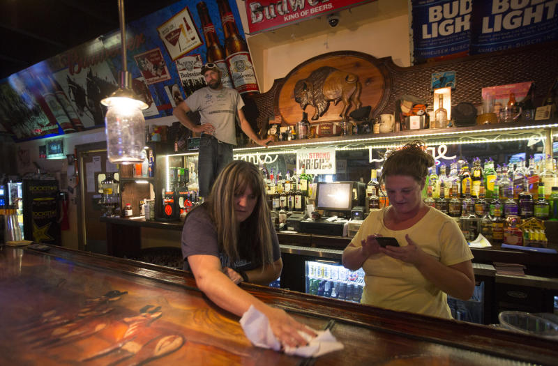 """Lori Sanders, a bartender at Hank's Roadside Bar and Grill in Wright,wipes down the bar.""""We don't put anybody to the side because of who they are,"""" she said of Wyomingites. (Josh Galemore/Casper Star-Tribune)"""