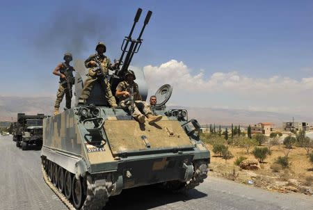 Lebanese army soldiers on armoured carriers and military vehilces advance towards the Sunni Muslim border town of Arsal, in eastern Bekaa Valley as part of reinforcements August 5, 2014. REUTERS/Hassan Abdallah