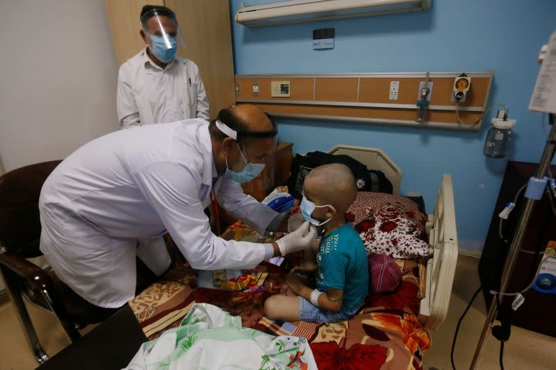 A nurse helps a child who suffers from cancer to wear a protective mask at the Children's Hospital for Cancer Diseases in Basra