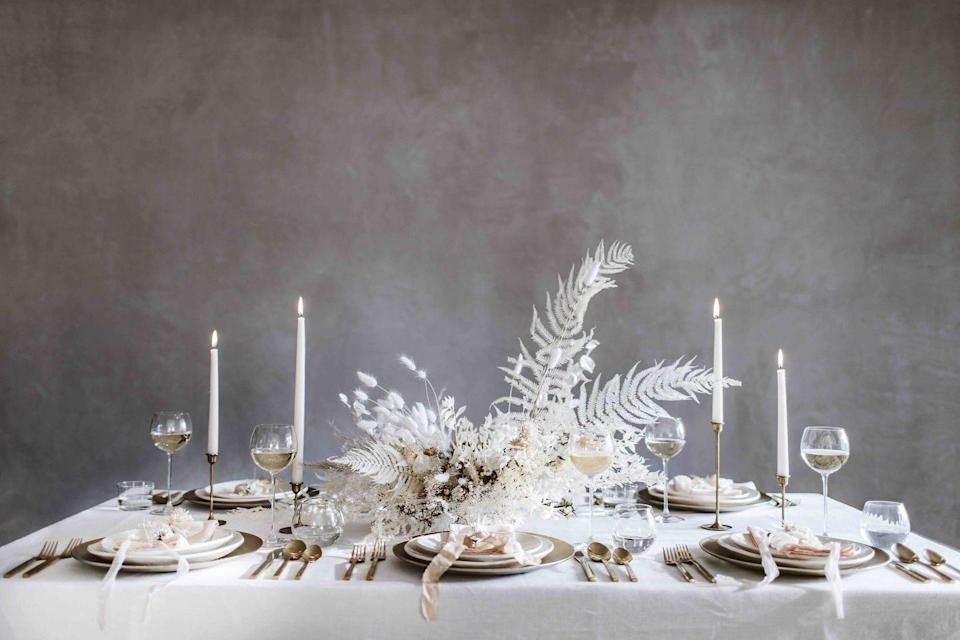 """<p>Create a Narnia-esque fairy-tale mood with an enchanting centrepiece of tonal dried flowers and bleached fern. See Beth Kirby's Local Milk blog for a guide to making your own</p><p>'Haydee' white linen <strong>tablecloth</strong>, approx £82; light pink linen <strong>napkins</strong>, approx £23 for a set of two, both Celina Mancurti (celinamancurti.com). Vintage brass <strong>candleholders</strong>, sourced from Etsy (etsy.com). For similar glasses, try 'Wine Balloon <strong>Glasses</strong>', £60 for a set of four, LSA International (lsa-international.com). For similar cutlery, try 'Gold <strong>Cutlery</strong>',£34 for a set of five; for plates, try 'Organic Shaped <strong>Dinnerware Set</strong>', from £4 for a plate, all West Elm (westelm.co.uk). For a similar charger, try the 'Maguelone Presentation <strong>Plate</strong>' in 'Grey Cashmere', £27, Amara (amara.com). Find silk <strong>ribbons </strong>at VV Rouleaux (vvrouleaux.com). For similar <strong>floral arrangements</strong>, try Worm (weareworm.com)</p><p><br></p><p><strong>This article first appeared</strong> <strong>in</strong> <a href=""""https://magsdirect.co.uk/magazine/elle-decoration-aug-20/"""" rel=""""nofollow noopener"""" target=""""_blank"""" data-ylk=""""slk:ELLE Decoration October 2020"""" class=""""link rapid-noclick-resp"""">ELLE Decoration October 2020</a></p><p><strong>Like this article?</strong></p><p> <u><a href=""""https://hearst.emsecure.net/optiext/optiextension.dll?ID=LKHLy4U%2BAPDM5JcrmOKxtYntAlN0FMNelBSKJmXANeFj7b3wVEXa8UQNxN3Kk5RyF_0Q89Kyk6%2BjLh"""" rel=""""nofollow noopener"""" target=""""_blank"""" data-ylk=""""slk:Sign up to our newsletter"""" class=""""link rapid-noclick-resp"""">Sign up to our newsletter</a></u> to get more articles like this delivered straight to your inbox.</p><p><a class=""""link rapid-noclick-resp"""" href=""""https://hearst.emsecure.net/optiext/cr.aspx?ID=vHKFu8HayrHGHrEU4cTJKHReN4RC9VjIt15XLnAcyuTVdQGHZT30HzJlcoyO9J57XlTSc_LbniD_vs"""" rel=""""nofollow noopener"""" target=""""_blank"""" data-ylk=""""slk:SIGN UP"""">SIGN UP</a></p><p>"""