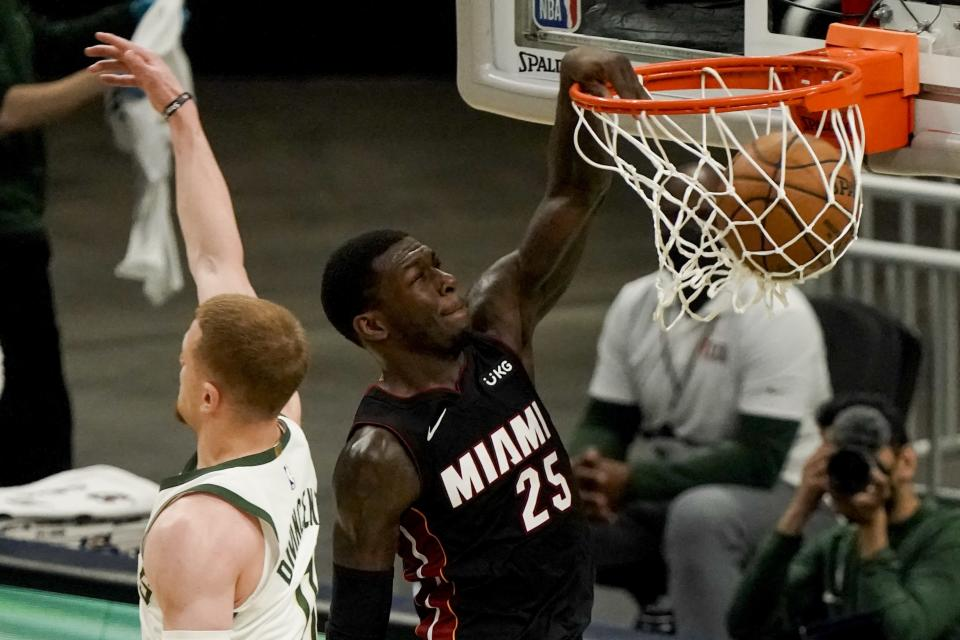 Miami Heat's Kendrick Nunn dunks past Milwaukee Bucks' Donte DiVincenzo during the second half of an NBA basketball game Saturday, May 15, 2021, in Milwaukee. (AP Photo/Morry Gash)