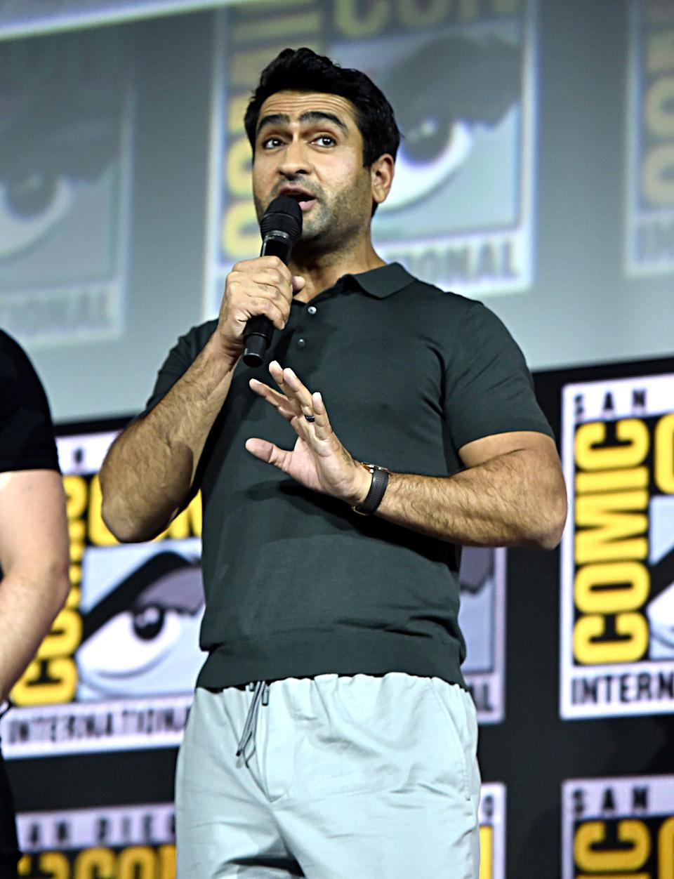 """""""Eternals"""" star Kumail Nanjiani speaking on stage at San Diego Comic-Con in 2019."""