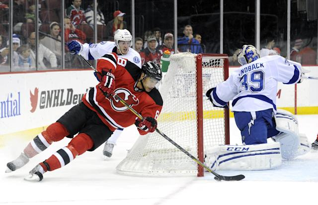 New Jersey Devils, Dainius Zubrus, left, of Lithuania, loses his edge as he skates around the net and attempts a shot against Tampa Bay Lightning goaltender Anders Lindback, of Sweden, during the second period of an NHL hockey game Saturday, Dec. 14, 2013, in Newark, N.J. (AP Photo/Bill Kostroun)