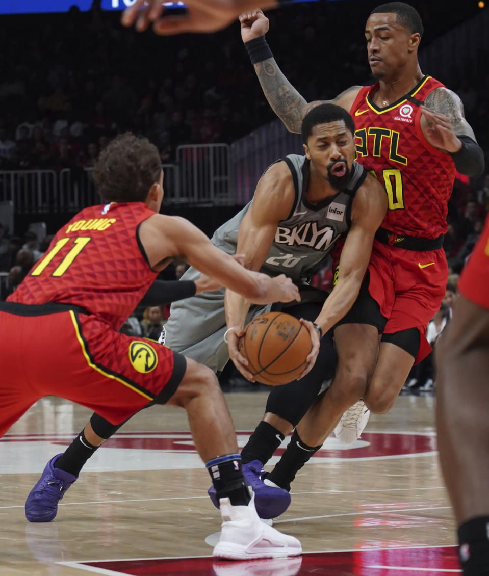 Brooklyn Nets Spencer Dinwiddie (26) tries to drive past Atlanta Hawks Trae Young (11) John Collins in the first half of an NBA basketball game Friday, Feb. 28, 2020, in Atlanta. (AP Photo/Tami Chappell)