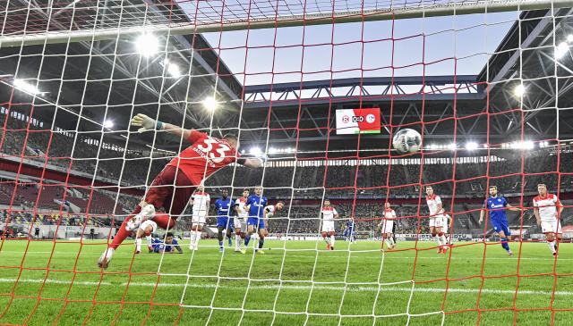 Schalke's Weston McKennie, left on the ground, scores the opening goal against Duesseldorf's goalkeeper Florian Kastenmeier during the German Bundesliga soccer match between Fortuna Duesseldorf and FC Schalke 04 in Duesseldorf, Germany, Wednesday, May 27, 2020. The German Bundesliga becomes the world's first major soccer league to resume after a two-month suspension because of the coronavirus pandemic. (AP Photo/Martin Meissner, Pool)