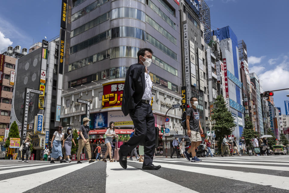 TOKYO, JAPAN - JULY 29: People wearing face masks cross a street on July 29, 2021 in Tokyo, Japan. Fans have been barred from most Olympic events due to the Covid-19 pandemic, which also caused the Games' yearlong postponement. (Photo by Yuichi Yamazaki/Getty Images)