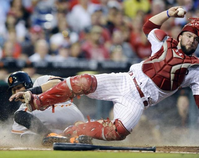 Philadelphia Phillies catcher Cameron Rupp trips over San Francisco Giants' Michael Morse who is forced out at home on a Ryan Vogelsong ground out to third in the fourth inning of a baseball game on Monday, July 21, 2014, in Philadelphia. (AP Photo/Michael Perez)