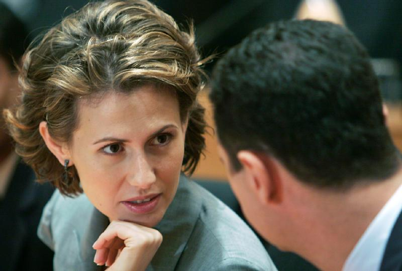 FILE - In this Friday, June 20, 2008 file photo, Syrian President Bashar Assad, right, listens to his wife Asma Assad during their visit to the campus of Infosys Technologies Ltd., an Indian software services company, in Bangalore, India. As Syria's bloodshed deepens, the country's British-born first lady has become an object of contempt for many, a Marie Antoinette figure who shopped online for fondue sets and 6-inch, crystal-encrusted Christian Louboutin heels while her country burned. The EU has slapped sanctions on Asma Assad, the young, stylish wife who for a decade offered a veneer of respectability to one of the world's most secretive and ruthless dictatorships.(AP Photo/Aijaz Rahi)