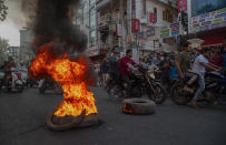 Indian protesters burn tires on a road during a shutdown protest against the Citizenship Amendment Bill (CAB) in Gauhati, India, Tuesday, Dec. 10, 2019. Opponents of legislation that would grant Indian citizenship to non-Muslim illegal migrants from Pakistan, Bangladesh and Afghanistan have enforced an 11-hour shutdown across India's northeastern region. (AP Photo/Anupam Nath)