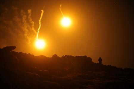 Flares are seen in the sky during fighting in the Islamic State's final enclave, in the village of Baghouz, Deir Al Zor province, Syria March 11, 2019. REUTERS/Rodi Said