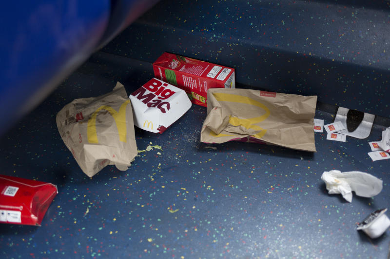 Dropped McDonalds packaging and food remains on the floor of a London bus.