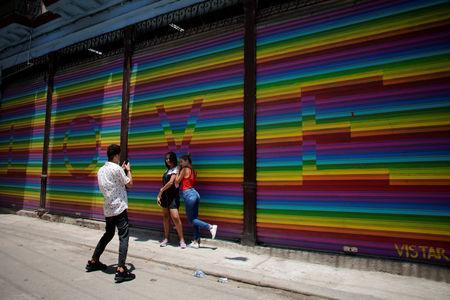 People pose for photos in front of a painting with the colors of the rainbow flag in Havana, Cuba, May 7, 2019. REUTERS/Alexandre Meneghini