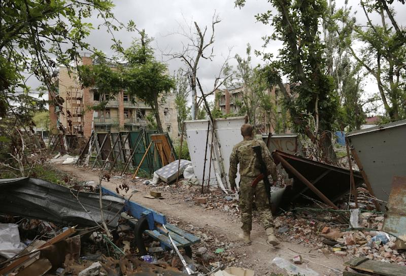 A Ukrainian serviceman walks along boards used a protection against snipers in Shyrokyne, Donetsk region on June 29, 2015 (AFP Photo/Anatolii Stepanov)