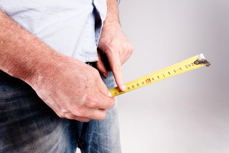 An unrecognizable man's hands hold a tape measure to the crotch of his jeans, checking size or growth with his forefinger.