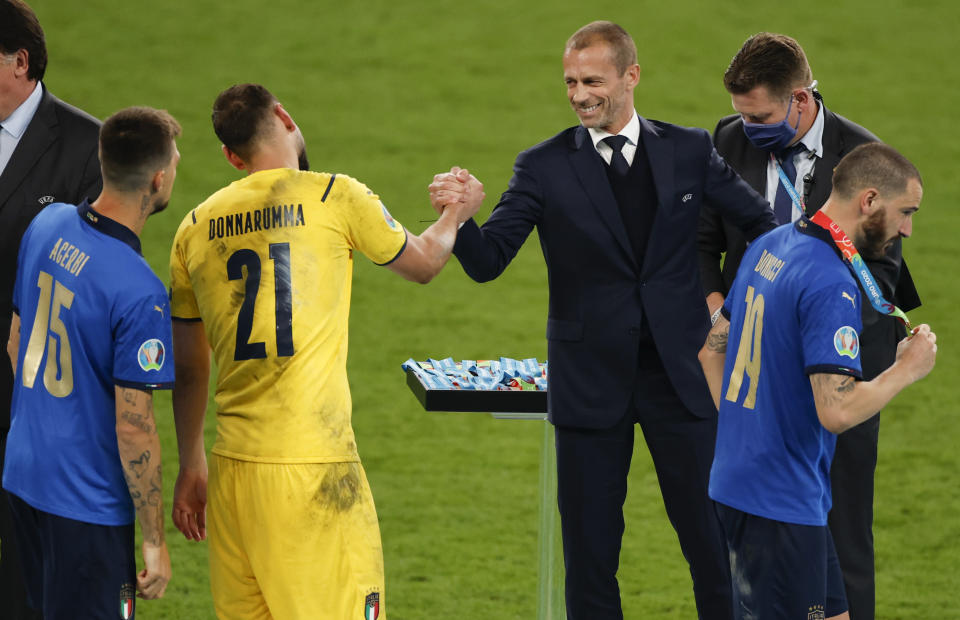 President of UEFA Aleksander Ceferin congratulates Italy's goalkeeper Gianluigi Donnarumma after they defeated England on the Euro 2020 soccer championship final at Wembley stadium in London, Sunday, July 11, 2021. (John Sibley/Pool Photo via AP)