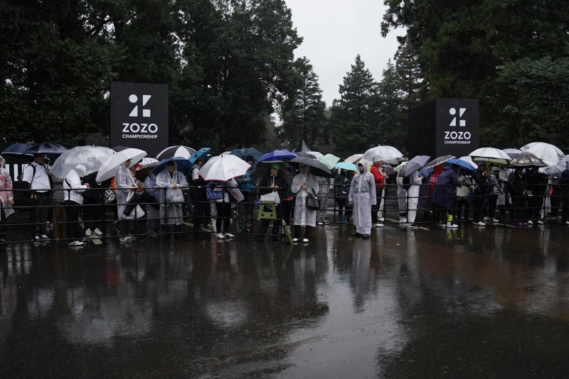 Spectators wait for shuttle buses in the rain at the gate after the second round of the Zozo Championship PGA Tour is postponed due to heavy rain at the Accordia Golf Narashino country club in Inzai, east of Tokyo, Japan, Friday, Oct. 25, 2019. Organizers on Friday postponed the second round of the Zozo Championship in Japan due to heavy rain. (AP Photo/Lee Jin-man)