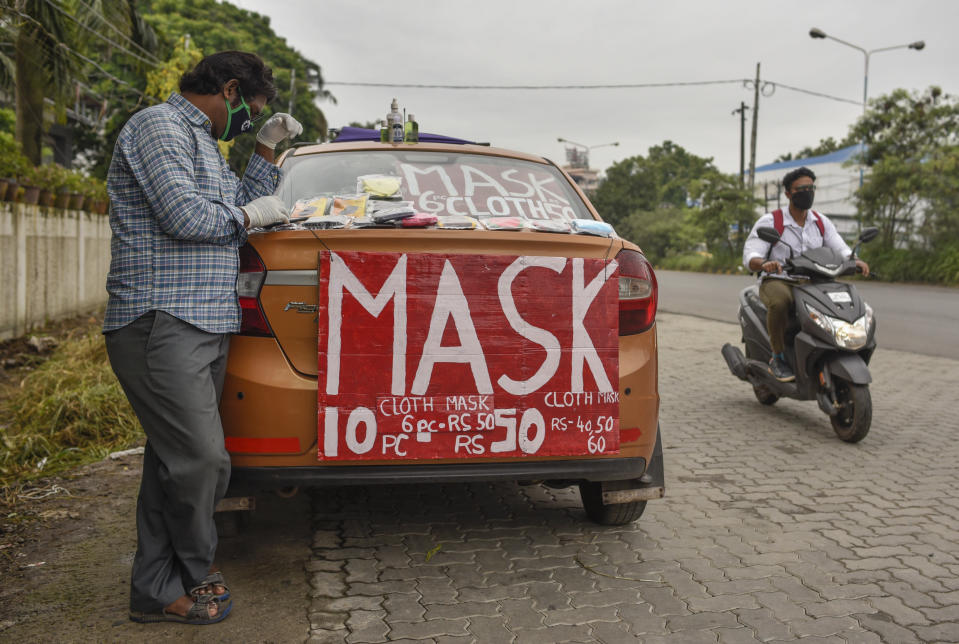 An Indian cab driver who has been out of work due to the COVID-19 pandemic, sells face masks from his car by a roadside in Kochi, Kerala state, India, Thursday, July 2, 2020. (AP Photo/R S Iyer)