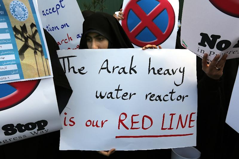"An Iranian student holds a placard reading, ""The Arak heavy water reactor is our red line"" during a demonstration outside in Tehran on November 23, 2014, to show support to Iran's nuclear programme"