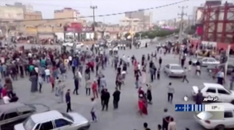 In this Saturday, Nov. 16, 2019 image from video aired by Iran's Islamic Republic of Iran Broadcasting state television channel, protesters gather on a street in Khorramshahr, Iran. Protesters angered by Iran raising government-set gasoline prices by 50% blocked traffic in major cities and occasionally clashed with police Saturday after a night of demonstrations punctuated by gunfire, violence that reportedly killed at least one person. (IRIB via AP)