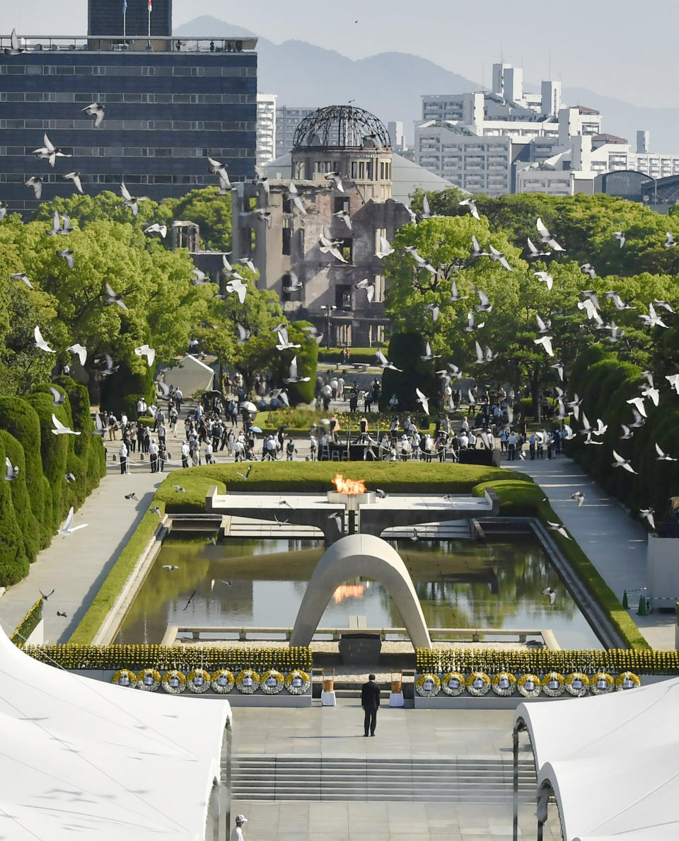 Doves fly over the cenotaph dedicated to the victims of the atomic bombing during a ceremony to mark the anniversary of the bombing at Hiroshima Peace Memorial Park in Hiroshima, western Japan Friday, Aug. 6, 2021. Hiroshima on Friday marked the 76th anniversary of the world's first atomic bombing of the city. (Shingo Nishizume/Kyodo News via AP)