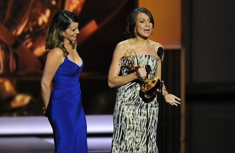 "Tina Fey, left, and Tracey Wigfield accept the award for outstanding writing for a comedy series for their work on ""30 Rock"" at the 65th Primetime Emmy Awards at Nokia Theatre on Sunday Sept. 22, 2013, in Los Angeles. (Photo by Chris Pizzello/Invision/AP)"